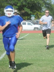Abilene Police Chief Stan Standridge, right, runs with