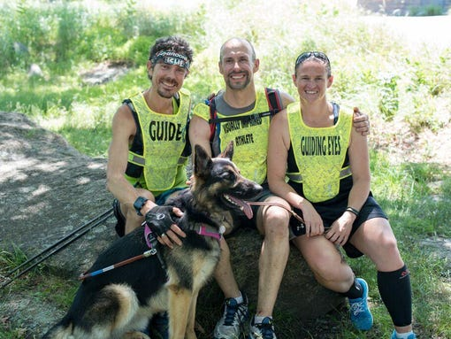 Image of ultra-marathoner Scott Jurek with Guiding Eyes CEO Thomas Panek and guide dog instructor Jolene along with guide dog Klinger.