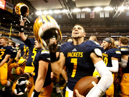 Ithaca quarterback Jake Smith celebrates his team's 27- 20 victory over Clinton  in the Division 6 title game at Ford Field on Nov. 27, 2015.