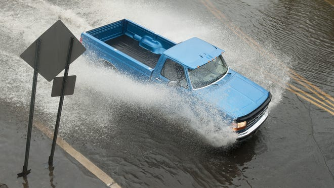 A motorist navigates through a flooded portion of the Brooklawn Circle as heavy rain falls on Wednesday afternoon.