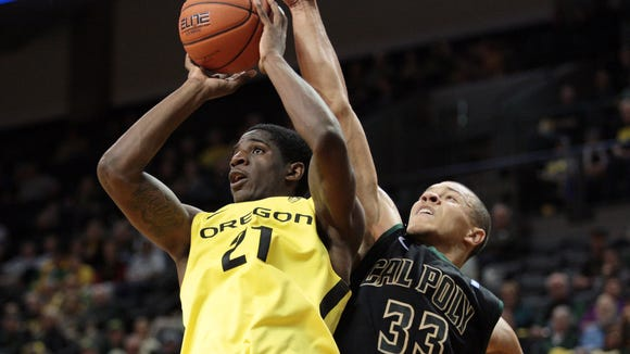 Dec 1, 2013; Eugene, OR, USA; Oregon Ducks guard Damyean Dotson (21) shoots the ball against Cal Poly Mustangs forward Chris Eversley (33) at Matthew Knight Arena. Mandatory Credit: Scott Olmos-USA TODAY Sports