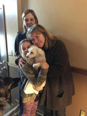 In this photo provided by Jessica Hartman, Monica Newhard, right, and her granddaughter, Helen Welch, hold their pet bichon frise, Zoey, as the dog's rescuer, Christina Hartman, stands behind them, Wednesday, Jan. 3, 2018, in Palmerton, Pa. Newhard's brother says an eagle snatched Zoey from the yard.