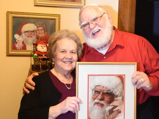 Janice Harris, left, and her husband Johnny hold up the first photo professionally taken of him as Santa Claus in Mountain Home. The 75-year-old man had appeared in the Mountain Home Christmas parade as Santa since 1990. The Harris family, Mr. and Mrs. Claus, also visited families who requested their presence for Christmas gatherings.
