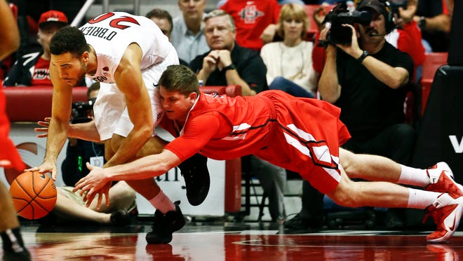 Ball State forward Matt Kamieniecki tackles San Diego State forward J.J. O'Brien, left, while trying to capture a loose ball during the first half of an NCAA college basketball game Saturday, Dec. 20, 2014, in San Diego. Kamieniecki was called for the foul. (AP Photo/Lenny Ignelzi)