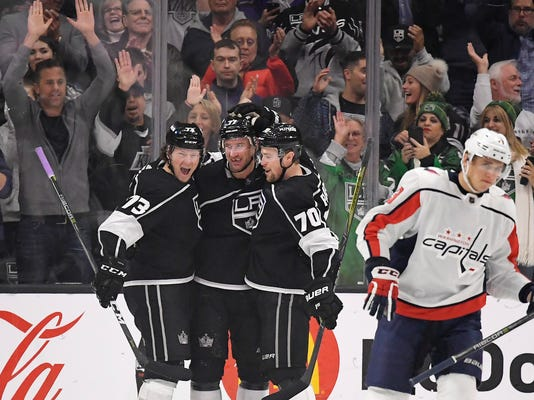 Los Angeles Kings center Jeff Carter, second from left, celebrates his goal with center Tyler Toffoli, left, and left wing Tanner Pearson, second from right, as Washington Capitals left wing Jakub Vrana, of the Czech Republic, skates off during the first period of an NHL hockey game, Thursday, March 8, 2018, in Los Angeles. (AP Photo/Mark J. Terrill)
