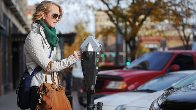 Karla Santi, of Sioux Falls, pays a parking meter along Phillips Avenue after parking her car Tuesday. The city council is debating raising rates for parking meters and some parking lots.