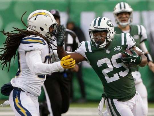 New York Jets running back Bilal Powell (29) fends off Los Angeles Chargers' Tre Boston (33) during the second half of an NFL football game Sunday, Dec. 24, 2017, in East Rutherford, N.J. (AP Photo/Seth Wenig)