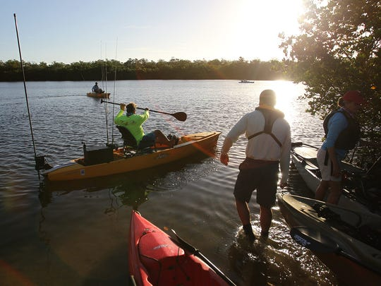 "John Donahue, left, takes out a Hobie fishing kayak along with other Hobie reps and local authors at J.N. ""Ding"" Darling National Wildlife Refuge on Sanibel."