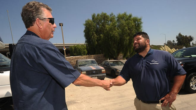 R&D Transportation Services president and CEO Charles Devlin (left) shakes hands with Charles Sandlin, owner of Roadrunner Shuttle & Limousine Service at the company's Camarillo facility.