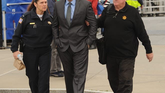 Jorge Adames-Garcia, center, is escorted off the Steamship Authority's fast ferry in May 2016 after his hearing in Nantucket Superior Court. Adames-Garcia's attorney has appealed his rape and kidnapping convictions, saying the island jury was tainted.