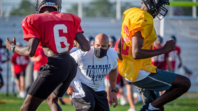 Truman football head coach Charlie Pugh, center, works with a pair of players, including senior quarterback Quincy Scott, right, during drills in practice Wednesday morning on the high school's field.