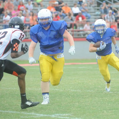 Mountain Home's Drew Strope tries to run around the left side during the Bombers' scrimmage last week at Highland.