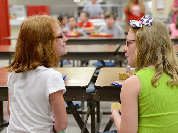 Norfork third grade students Cassandra Duffy (left) and Audrie Foreman talk during breakfast on Monday, Aug. 18, 2014, during the first day of school.