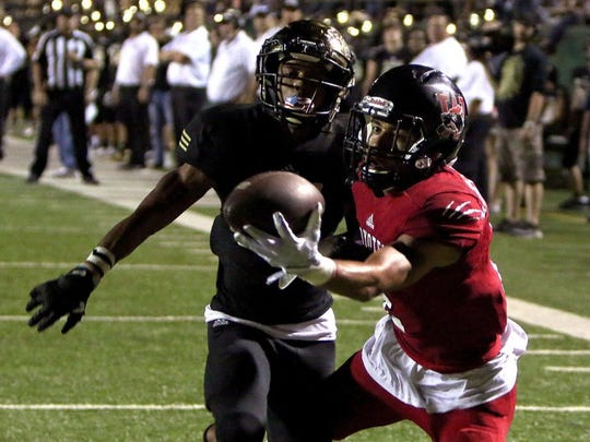 Wichita Falls High School's Jordan Hatton (right) makes a one-handed catch while falling into the end zone as Rider's Danari Curry tries to defend last season at Memorial Stadium. Hatton hopes to make another highlight-reel catch when the Coyotes face the Raiders on Friday.