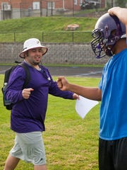Aaron Lamb, left, one of Waynesboro High School's football coaches, greets a player with a fist bump at the start the season's first practice on Monday, Aug. 4, 2014 in Waynesboro.