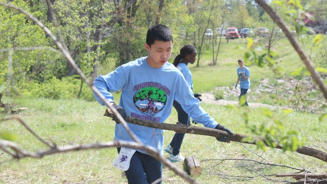 Kevin Yang, 12, a student at North Central Junior High, helps clear brush in North Liberty's Joy's Park for a school project on May 1, 2015.