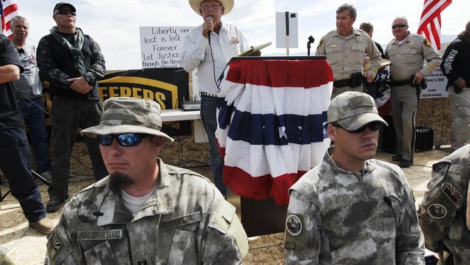 Nevada rancher Cliven Bundy, center, addresses his supporters along side Clark County Sheriff Doug Gillespie, right, while being guarded by militia members last year. Bundy on Friday denied he was involved in an incident in the Gold Butte area southwest of Mesquite on June 5 in which three Bureau of Land Management contractors claim shots were fired near their camp on two occasions one night.