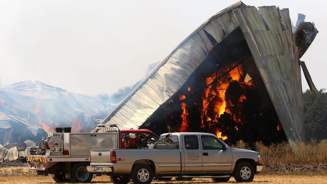 A hay barn burns north of Lebanon, on Wednesday, Aug. 12, 2015. Members of the Lebanon Fire District responded to the blaze early Tuesday morning. Attempts to douse the fire, made up of 2000 tons of straw, proved futile and the department has decided to let it burn while they monitor it.