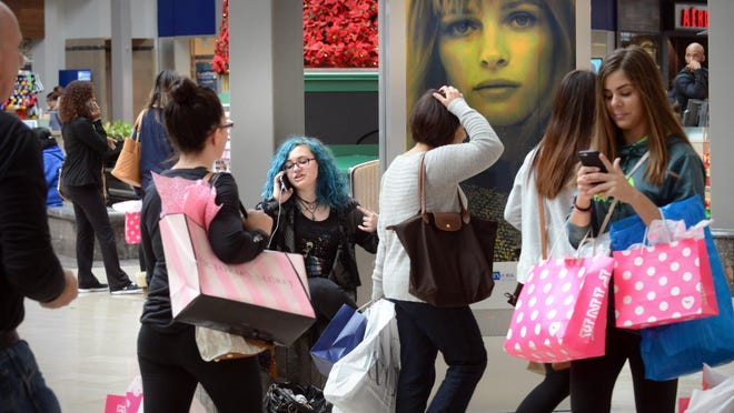 People shop on Black Friday at the Willowbrook Mall in Wayne, N.J. Shoppers heading to stores armed with their smartphones need to beware of cybercriminals, who may attempt to steal personal data.
