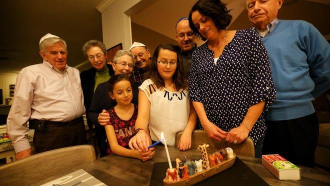 Alan and Ann Hamburger, Helen and John Lamar and Stuart Fox look on, as Dan, Margo, Hailey, 12, and Avery Fox, 8, light the menorah for Hanukkah, the eight-day religious holiday celebrated by Jews.