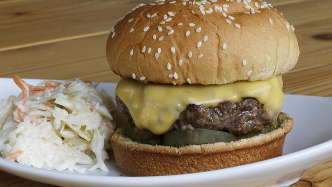 This April 2016 photo shows a grilled cheeseburger in Concord, N.H. Consider a cast-iron grill platter, a thick, flat sheet of cast iron, to grill up the perfect summer burger. (AP Photo/J.M. Hirsch)