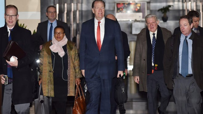"""US Undersecretary for International Affairs David Malpass (C) leaves a hotel with members of a negotiation team on the way to trade talks in Beijing on February 12, 2019. - Negotiators headed to a second day of trade talks on February 12, hoping to reach a deal before the March 1 deadline set by Donald Trump as the IMF warned of a possible global economic """"storm""""."""