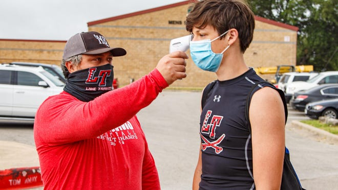 Lake Travis Cavaliers linebacker David van Heijningen passes the temperature check by cornerback coach Robert Rayos before entering the field for summer conditioning workouts on June 18 at Lake Travis High School.