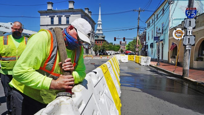 Glenn Kelleher, left, and Jeff Boucher of the Portsmouth Public Works Department fill portable barriers with water Tuesday, around the Clipper Tavern on Pleasant St. to create outdoor seating.