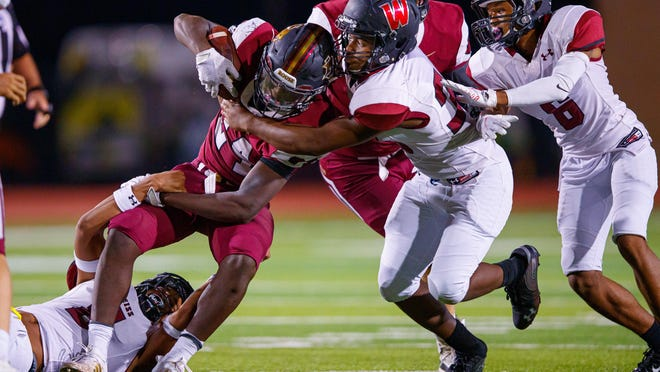 Rouse running back EJ Moore is pulled down by Weiss defenders during the third quarter at the nondistrict football game on Thursday at Bible Memorial Stadium. Moore ran for 126 yards and four touchdowns in Rouse's win.