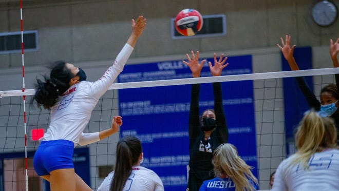 Westlake Chaparrals outside hitter Sophia Luo, left, hits the ball across the net against Austin High Sept. 29 at Westlake High School.  Luo, a sophomore, had 12 kills in the win over the Maroons.