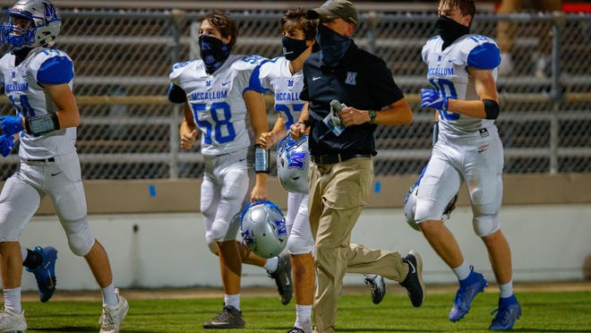 The McCallum football team, led here by coach Thomas Gammerdinger before a game against Anderson, has had its game Friday postponed because of COVID-19 concerns on campus.