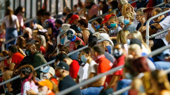 Fans in Georgetown wear masks and watch the game between the East View Patriots and the Elgin Wildcats last Friday in Georgetown. Weeks after Gov. Greg Abbott loosened coronavirus restrictions for businesses in much of the state, the Texas Department of State Health Services says the number of new cases and hospitalizations is on the rise.