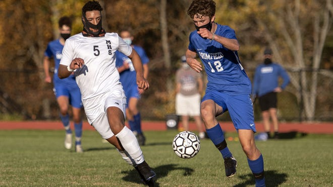 Bromfield senior Dylan Winchell brings the ball up the field, as Marlborough senior Philipe Cruz pursues him, during the game in Harvard, Oct. 9, 2020. The Panthers beat the Trojans, 3-1. After going fully remote on Oct. 19, Marlborough sports will resume next week.