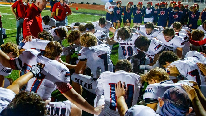 Prayers such as this one being made by the coach and players of the Wimberley High School in Texas could be carried on the public-address system before Florida High School Athletics Association championship games if a new bill passes the Florida Legislature.