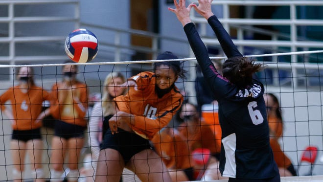 Westwood Warriors outside hitter Payton Feree fires a kill past Austin High setter Kasen Rosenthal during the third set at the Class 6A bidistrict volleyball playoff match Nov. 19 at the Burger Center in Austin. Westwood won in three sets.
