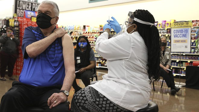 Gov. Steve Sisolak receives his COVID-19 vaccine from pharmacy manager Trashelle Miro alongside front-line grocery store workers at an Albertsons Pharmacy in Las Vegas on March 11.