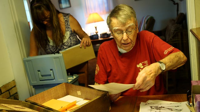 Howard Hobbs, a World War II veteran and former POW, lives with his daughter, Sharon Ball. They are sorting through his records, looking for a photo of himself from World War II.