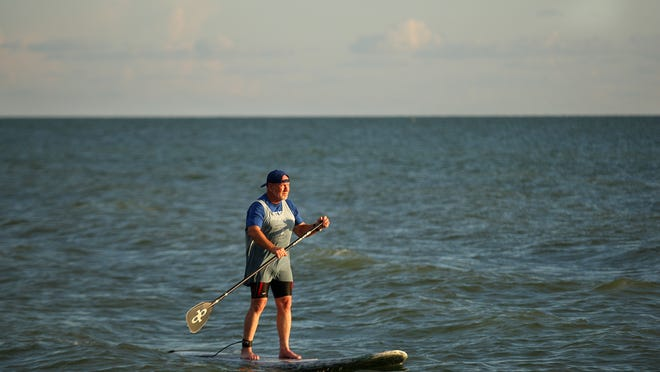 Randy Wayne White stand-up paddleboards recently on Sanibel Island.