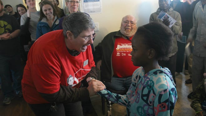 Iowa Valley Habitat for Humanity construction manager Christy Shipley gave Sifu Mausa the keys to her family's new home during a dedication ceremony on Nov. 8, 2014.