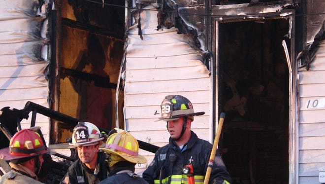 Firefighters take a break from the heat of a fire at 1027 Ann St. in Newport Friday evening.