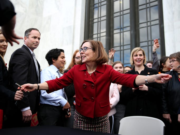 Gov. Kate Brown gives out pens she used to sign HB