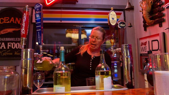 Jody Jones, general manager at the Cracker Box in Fort Myers, prepares a few drinks for customers while working  Friday evening. Her family has owned the restaurant since 1975. The cozy restaurant is renowned for its live music and local color.