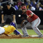 LSU outfielder Andrew Stevenson dives back to first base as UL Lafayette first baseman Greg Davis attempts to tag him out during the Tigers' 8-6 win over the Cajuns Tuesday night in the Wally Pontiff Classic in Zephyr Field in Metairie.