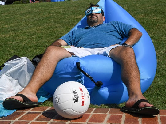 Andrew Police of Peachtree City, Georgia takes a nap in the sun and covers his eyes with Eclipse brand gum paper wrapper during the solar eclipse event at Clemson University on Monday, August 21.