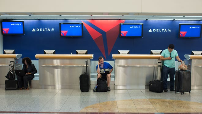 Passengers wait at Hartsfield–Jackson Atlanta International Airport, Monday, Aug. 8, 2016, in Atlanta. Delta Air Lines delayed or canceled hundreds of flights Monday after its computer systems crashed, stranding thousands of people on a busy travel day. (AP Photo/Branden Camp)