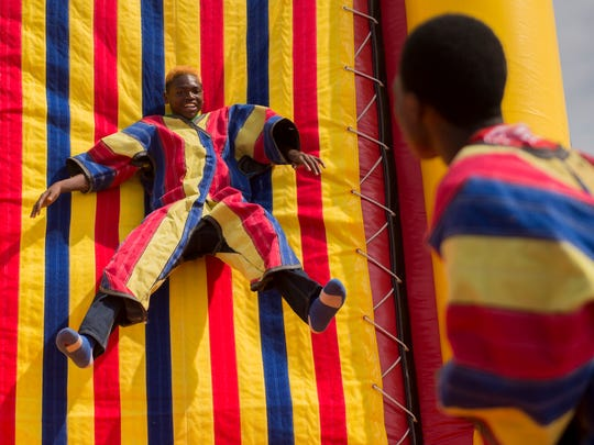 Kareem Sharif, center, 14, of Murfreesboro, sticks to a Velcro wall during Eid al-Fitr celebrations at the Islamic Center of Murfreesboro on Wednesday, July 6, 2016.