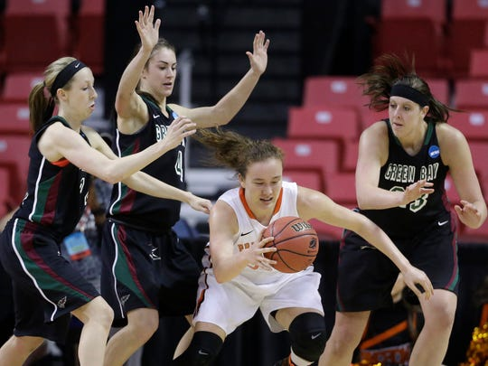 Princeton guard Michelle Miller, center, dribbles between Green Bay guard Allie LeClaire, from left, guard Kaili Lukan and center Lexi Weitzer in the second half of an NCAA college basketball game in the first round of the NCAA tournament, Saturday, March 21, 2015, in College Park, Md. Miller contributed a team-high 20 points to Princeton's 80-70 win. (AP Photo/Patrick Semansky)