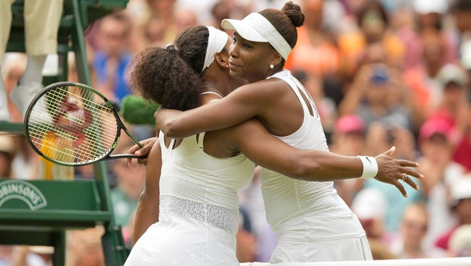 Serena Williams (USA) and Venus Williams  hug at the net after their match on day seven of Wimbledon.