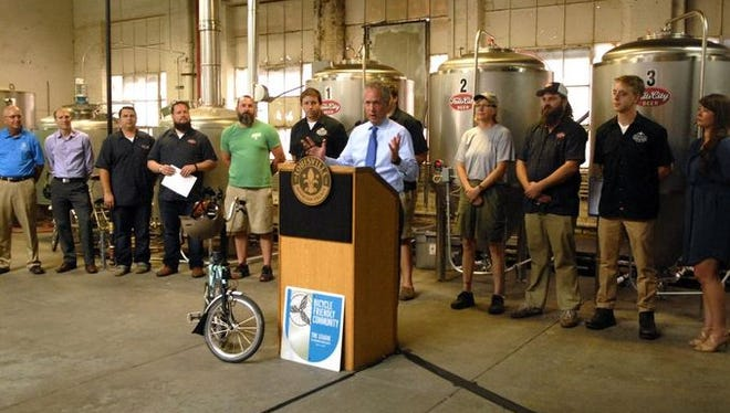Louisville Mayor Greg Fischer announced the city's new Craft Beer Trail Monday at Falls City Brewing. Reps from other local breweries stood behind him.