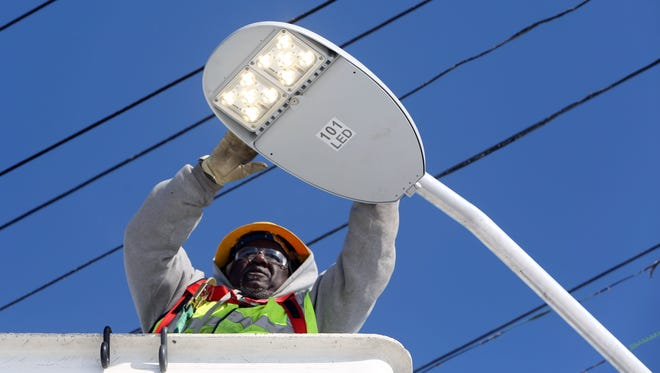 State Line Construction employee Danny West of Detroit installs a new LED light on a lamp post on Hamburg and Greiner in Detroit on Wednesday, February 12, 2014.